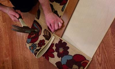 Woman hammering tack nails into board to secure a flowered area rug to wood for cat scratch board.